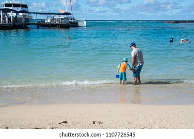 Waikiki Beach, Oahu, HI, USA 1-30-2018: Father and little boy son playing wading  in the gentle ocean waves at the beach near the boat dock