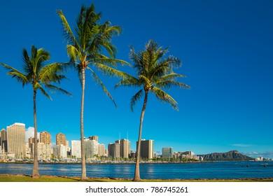 Waikiki beach skyline with diamond head, blue sky with white clouds