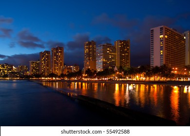 Waikiki beautiful palm lined tourist beach and beachfront hotels brightly lighted and reflected during blue hour in the evening in Oahu, Hawaii. Horizontal copy space