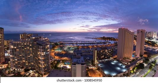 Waikiki city lights at sunset including views of the Ala Wai Small Boat Harbor, Magic Island, Hilton Hawaiian Village, Ilikai Hotel, Modern Honolulu, and Prince Hotel Honolulu