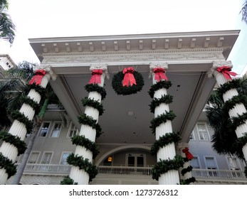 Waikiki - December 12, 2011: Christmas Wreath and Decorations with Red Bows hang from The Moana Hotel.  The Moana Hotel is a historic hotel building on the island of Oahu, at 2365 Kalākaua Avenue