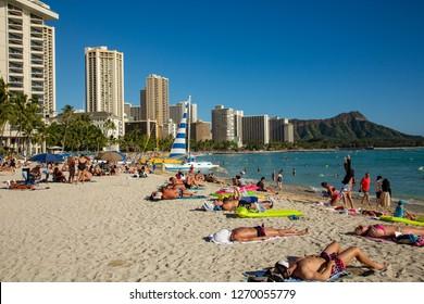 Waikiki, Hawaii - 2/9/2014:  Waikiki, Hawaii - 2/9/2014:  Sun bathers and swimmers on the beach in front of major hotels at Waikiki, Hawaii.