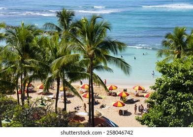 WAIKIKI, HAWAII - FEBRUARY 18, 2015: A unique view palm trees and beach umbrellas Waikiki beach in Honolulu, Hawaii. Waikiki white sand beach shoreline is Hawaii's most famous beach.