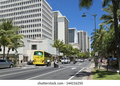 WAIKIKI, HAWAII - JUNE 15: Cars drive down Kalakaua avenue in Waikiki on June 15, 2013.  Waikiki is Oahus main hotel and resort area and a vibrant gathering place for visitors from around the world.