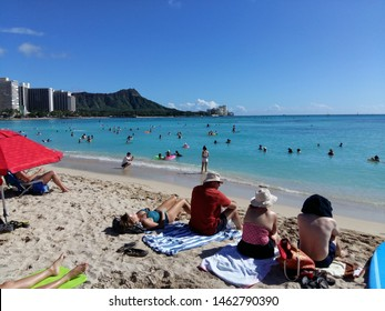 WAIKIKI, HAWAII - November 7, 2017: Tourists sunbathing and surfing on Waikiki beach in Honolulu, Hawaii. Waikiki white sand beach shoreline is Hawaii's most famous beach.