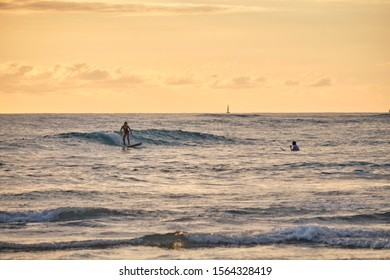 Waikiki, Hawaii / United States of America - January 16 2019: Surfers catching wave coming in at Waikiki