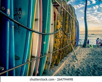 WAIKIKI, HI - APRIL 27: Surf board lines up on Waikiki beach at sunset on April 27, 2014 in Honolulu, USA. Waikiki beach is neighborhood of Honolulu, best known for white sand and surfing.