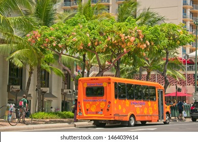 Waikiki, HI, USA - July 16, 2019: Hawaiian tour bus on Kalakaua Ave in Waikiki Beach.