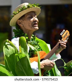 WAIKIKI, HONOLULU, HAWAII - March 26: An older local woman sings a Hawaiian song and plays the ukulele during the annual Prince Kuhio Day Parade on March 26, 2016 in Waikiki.