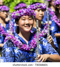 WAIKIKI, HONOLULU, HAWAII - SEPTEMBER 30, 2017: Unidentified members of a marching band wearing purple leis march through Waikiki during the annual Aloha Festivals Floral Parade.