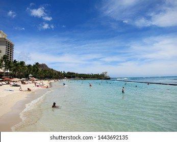 Waikiki- June 16, 2015: People play in the protected water and hang out on the beach in world famous tourist area Waikiki on a beautiful day with hotels in the distance in Waikiki, Hawaii.