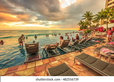 Waikiki, Oahu, Hawaii - August 20, 2016: people of infinity edge swimming pool, looking at the ocean sunset. Sheraton Waikiki Hotel in Waikiki Beach, Honolulu. Summertime relaxing in luxury resort.