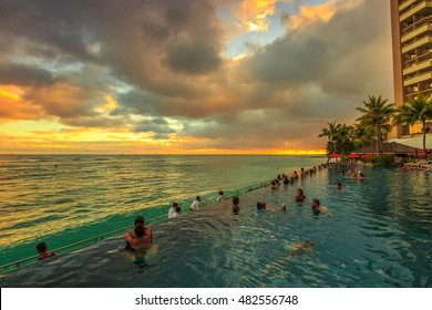 Waikiki, Oahu, Hawaii - August 20, 2016: people of infinity edge swimming pool, looking at the ocean twilight. Sheraton Waikiki Hotel in Waikiki Beach, Honolulu. Summertime relaxing in luxury resort.