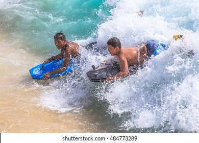Waikiki, Oahu, Hawaii - August 27, 2016: Little boys on vacation having fun swimming on boogie board at Waikiki Beach in Honolulu. The body boarding is the most popular water sports of Waikiki.