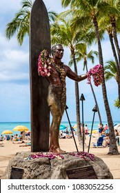 """Waikiki, Oahu, Hawaii / United States – January 20, 2018: Duke Kahanamoku iconic statue. Duke is considered """"The father of modern surfing"""", a master of swimming, surfing and outrigger canoe paddling."""