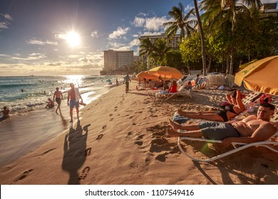 Waikiki, Oahu, Hawaii, United States - August 18, 2016: tourist sunbathing and walking on the shore on Waikiki beach at sunset. Waikiki beach, South Shore, is neighborhood of Honolulu of Hawaii.