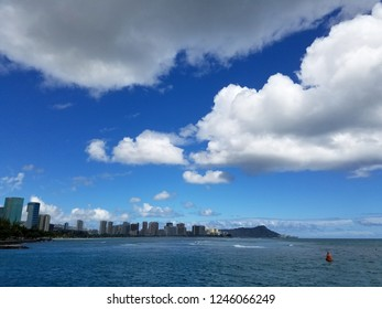Waikiki surf and Diamondhead during the day with hotels and surfers in the ocean on Oahu, Hawaii.