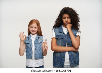 Wailful young dark skinned female with long curly hair leaning her chin on raised fist and looking regretfully at camera, standing over white background with red haired optimistic little girl
