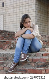 Wailful young woman sitting on the destroyed wall of the building