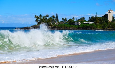 Waimea Bay, North Shore, Oahu, Hawaii  Beach, waves crashing on beach and over famous jumping rock and on the point.  Beach shows various warning signs and shore line with waves washing ashore.