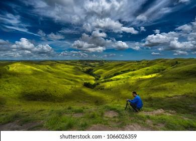 Wairinding hill, Waingapu, East Sumba, East Nusa Tenggara, Indonesia - March 2018 : A photographer setting up his tripod to shoot beautiful landscape.