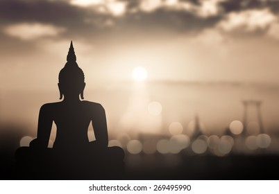 Waisak day concept: Sepia tone, silhouette Budha with blurred tourist attraction in thailand on sunset background