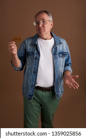 Waist up of the adult man in casual clothes standing isolated against the brown background and making helpless gesture with his hand