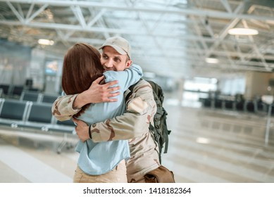 Waist up of American military man embracing his wife in waiting room. His spouse is glad to see him after long time apart. Homecoming and military concept
