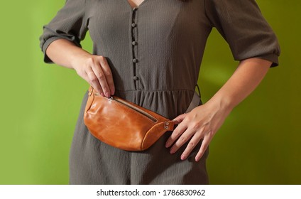 Waist bag made from natural leather close-up view on the unrecognizable woman on the green background. Concept of city accessoires and travel