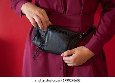 Waist bag made from natural leather close-up view on the unrecognizable woman on the green background. Concept of city accessoires and travel. Red color