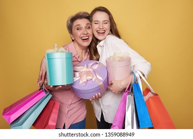 Waist up of beautiful ladies keeping colorful paper bags and presents on yellow background in studio. Charming brunette daughter is hugging her mother while posing for camera indoors. Happy Mothers