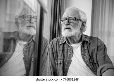 Waist up black-and-white portrait of thoughtful bearded man expressing nostalgia while resting. He is squinting eyes