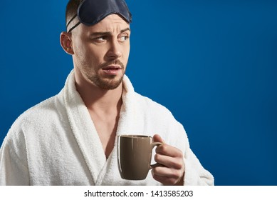 Waist up of Caucasian bearded guy wearing white bathrobe and night eye patches while holding cup with tea against blue background. Cropped shot of male model posing for camera while looking away in