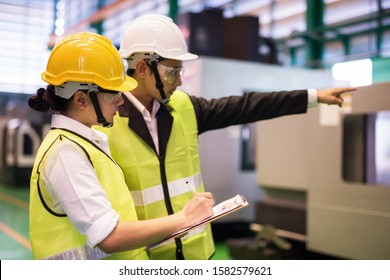 Waist up female factory worker write implement audit result of industrial machine while manager point finger to machinery. Manufacturing industry to produce car spare parts. Quality assurance (QA).