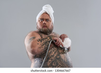 Waist up of funny surprised fat man standing isolated on the grey background and pressing shower head with shower puff to his tattooed belly