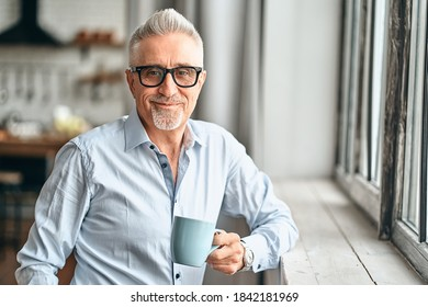 Waist up of handsome mature man in in a blue shirt leaning on the windowsill while holding coffee at his home. Leisure and lifestyle concept