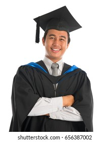 Waist up happy Asian male university student in graduation gown smiling, isolated on white background. Good looking Southeast model.