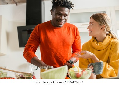 Waist up of man cooking in the kitchen and looking at the smiling girlfriend standing with a cup of tea
