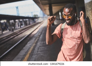 Waist up photo of afro-american man dancing to his favourite tune at railway station. Copy space in left side