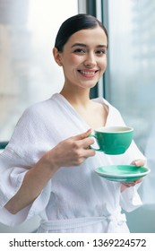 Waist up photo of the cheerful lady looking glad and smiling while being with a cup of tea in her hand