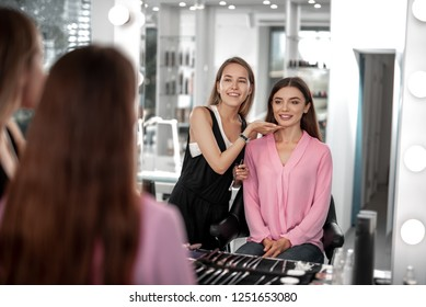 Waist up photo of professional stylist and beautiful girl looking at finished makeup in front of the mirror