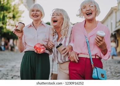 Waist up photo of stylish women holding cardboard glasses. White-haired females have fun together