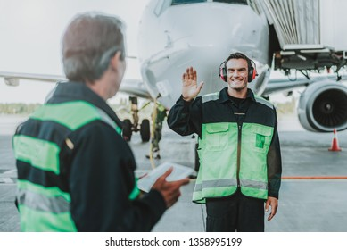 Waist up photo of two men from technical staff standing in aerodrom. Male in green waistcoat turning back and looking at colleague