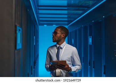 Waist up portrait of African American data engineer holding digital tablet while working with supercomputer in server room lit by blue light, copy space
