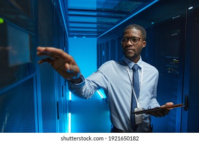 Waist up portrait of African American man reaching for server cabinet while working with supercomputer in data center and holding tablet, copy space
