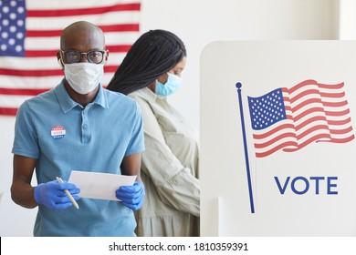 Porträt des afroamerikanischen Mannes aufwachen, der am Wahlstand steht, mit der Flagge der USA dekoriert und am Wahltag nach der Pandemie Kamera ansieht, Kopienraum