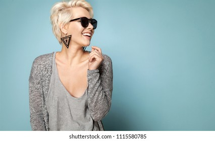 Waist up portrait of attractive blonde in stylish clothes and sunglasses. Lovely female laughing and looking away. Copy space in right side. Isolated on blue background