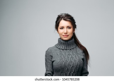 Waist up portrait of attractive brunette with nice long hair and lovely brown eyes. Pretty girl looking in camera with happiness and calmness. Isolated on gray background
