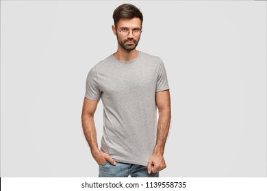 Waist up portrait of attractive fashionable male in stylish clohtes, glasses, keeps hand in pocket, looks seriously directly at camera, ready for walk, isolated over white background. People, fashion
