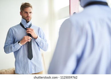 Waist up portrait of attractive male standing in front of mirror and clothing in morning. He is putting on tie with serious look